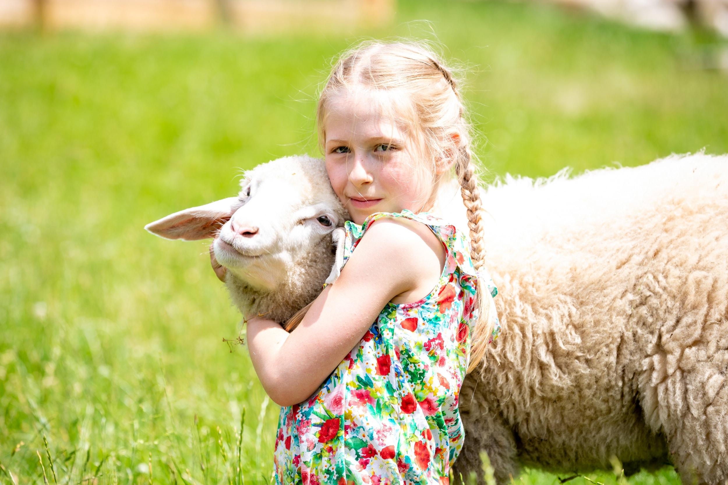 Mädchen kuschelt mit Schaf